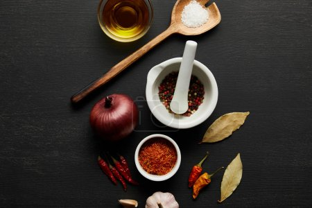 Top view of spices, olive oil with salt and bay leaves on black wooden background