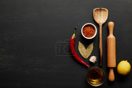 Top view of wooden rolling pin and spoon with spices and olive oil on black wooden background