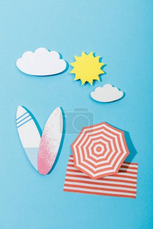 Top view of paper cut beach with surfboards, umbrella and blanket on blue background