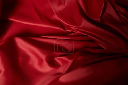 close up view of red soft and crumpled silk textured cloth