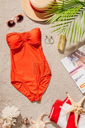 top view of stylish red swimsuit with magazine and accessories lying on sandy beach