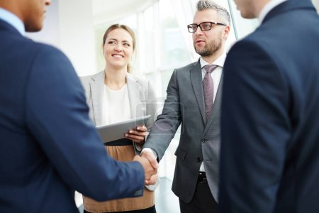 Happy businesspeople striking deal with partner