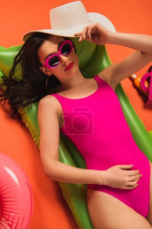 top view of beautiful woman in sunglasses and swimsuit lying on inflatable mattress and holding straw hat on orange