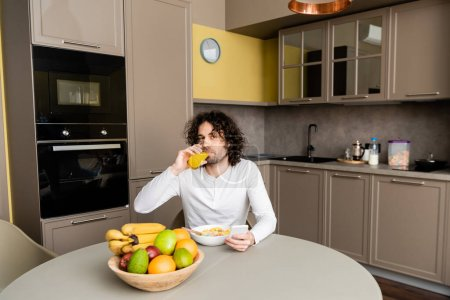 handsome man looking at camera while drinking orange juice and using smartphone during breakfast