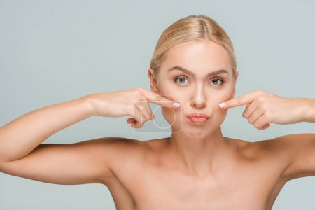 naked woman pointing with fingers at clean face isolated on grey
