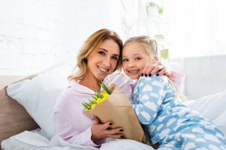 smiling mother with bouquet hugging daughter in mothers day