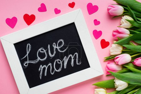Top view of chalkboard with love mom lettering near paper hearts and tulips on pink background