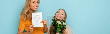 panoramic shot of happy mother holding greeting card with happy mothers day lettering near daughter isolated on blue