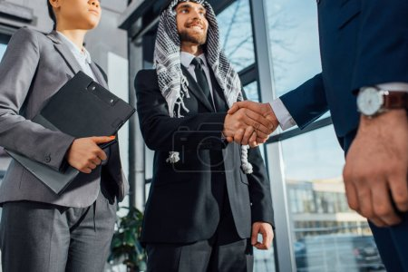cheerful arabic businessman shaking hands with partner on meeting with translator in office