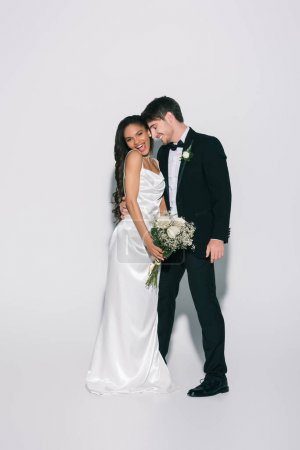 full length view of happy bridegroom hugging elegant african american bride holding wedding bouquet on white background