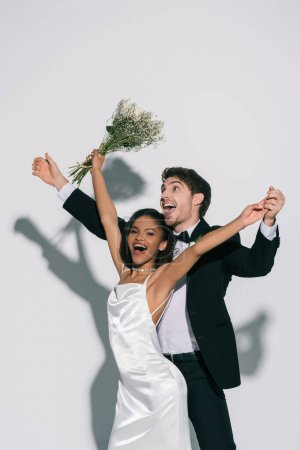 excited, elegant interracial newlyweds dancing on white background