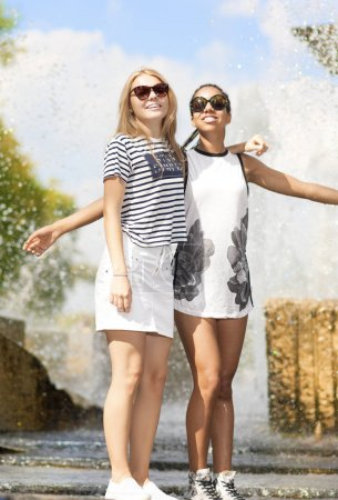Teenagers Concepts. Two Funny and Laughing Teenage Girlfriends Embracing Together. Posing Against Fountain