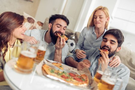Smiling friends eating pizza and drinking beer at home