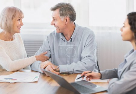 Mature couple talking to financial advisor at home
