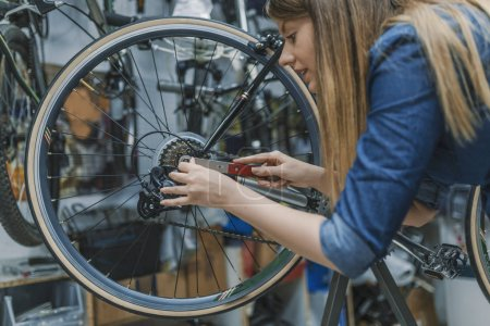 Mechanic repairing gears of bicycle in service shop.