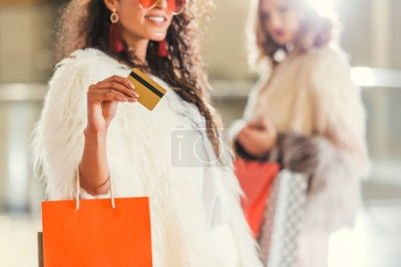 young woman with her shopping buddy in fur coat holding golden credit card