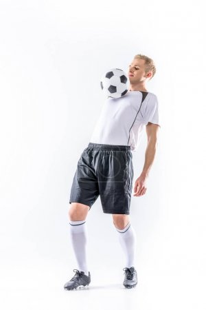 Soccer player exercising with ball