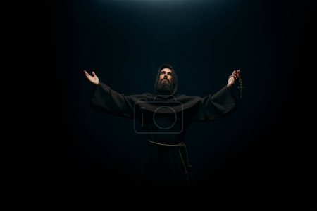 Medieval monk praying to the holy god, religion. Mysterious friar in dark cape, Mystery and spirituality