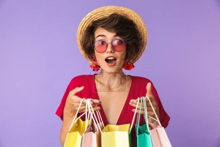 Image of excited brunette woman 20s in straw hat holding colorful paper shopping bags isolated over violet background