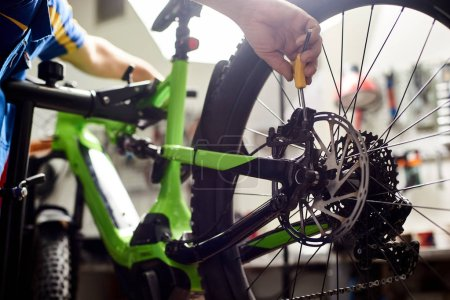 close up of male serviceman repairing modern bike brakes using special tool, wearing protective work wear