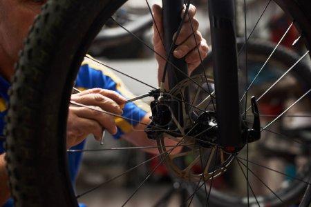 male mechanic making service in bicycle repair shop, repairman fixing bike brakes using special tool