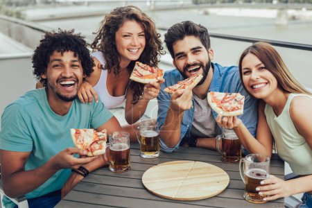Friends enjoying pizza. Group of young cheerful people eating pizza and drinking beer while sitting at the bean bags on the roof of the building