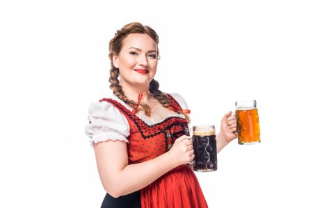 smiling oktoberfest waitress in traditional bavarian dress showing mugs with light and dark beer isolated on white background