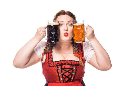 oktoberfest waitress in traditional bavarian dress holding mugs with light and dark beer isolated on white background