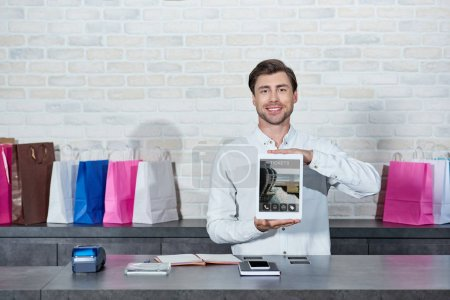 handsome young salesman holding digital tablet with tickets application and smiling at camera in shop