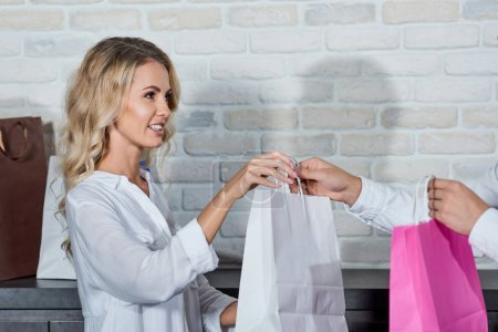 cropped shot of smiling young woman giving shopping bag to colleague in store