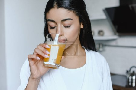 beautiful mixed race girl in white robe drinking fresh orange juice in morning in kitchen with closed eyes