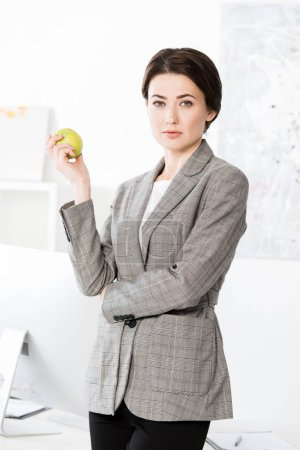 attractive businesswoman in grey suit holding apple and looking at camera in office