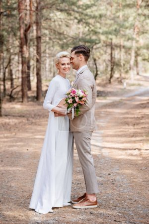 full length view of just married couple embracing in forest