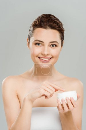 happy woman smiling while holding container with face cream isolated on grey