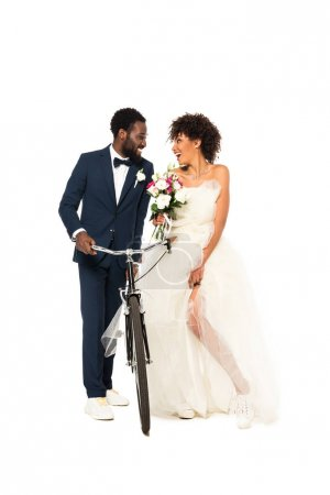 happy african american bridegroom near cheerful bride with flowers holding bicycle isolated on white