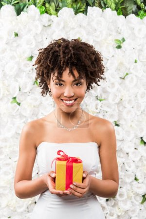 cheerful curly african american bride holding present near flowers