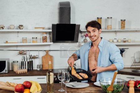 sexy smiling man holding frying pan with fish in kitchen