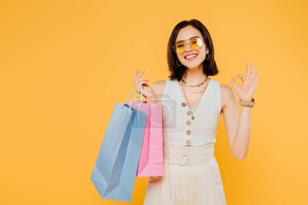 happy fashionable girl in sunglasses holding shopping bags and showing okay sign isolated on yellow