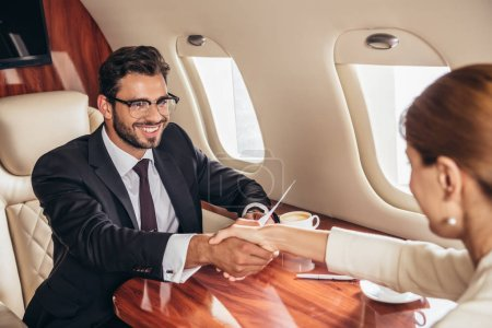 smiling businessman and businesswoman shaking hands in private plane