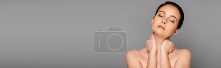beautiful naked woman with perfect skin and closed eyes touching neck isolated on grey, panoramic shot