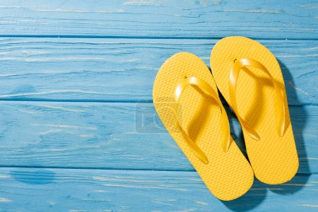 top view of yellow flip flops on wooden blue background