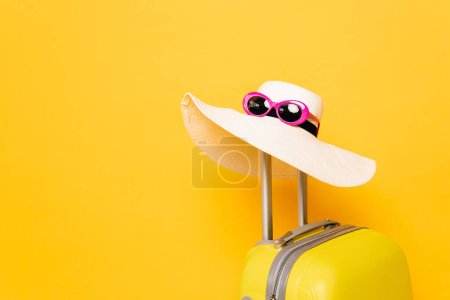 sun hat and sunglasses on suitcase handle on yellow background