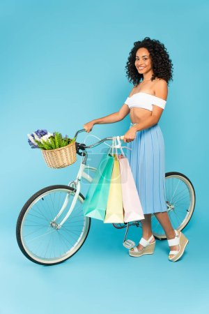 cheerful african american girl standing near bicycle with shopping bags on blue, summer concept