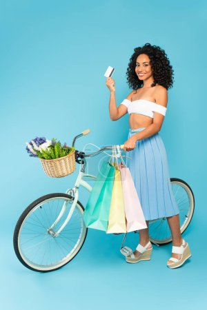 cheerful african american girl standing near bicycle and holding credit card and shopping bags on blue, summer concept