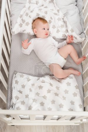 top view of infant boy in baby romper lying in crib
