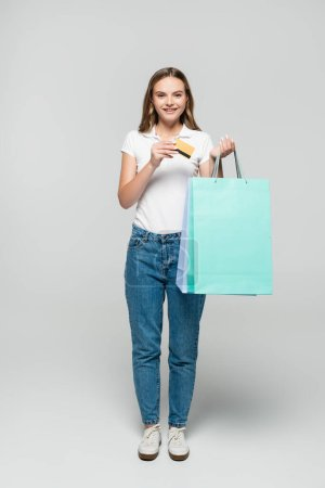 joyful young woman holding credit card and blue shopping bags on grey, black friday concept