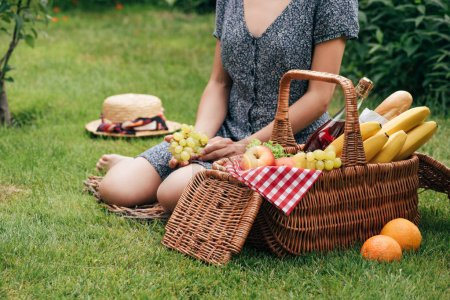 cropped image of woman sitting on green grass at picnic and holding grapes