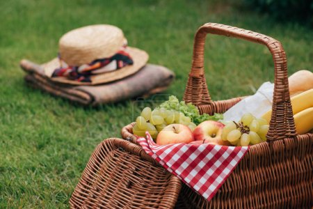 delicious fruits in basket on green grass at picnic, hat and blanket on background