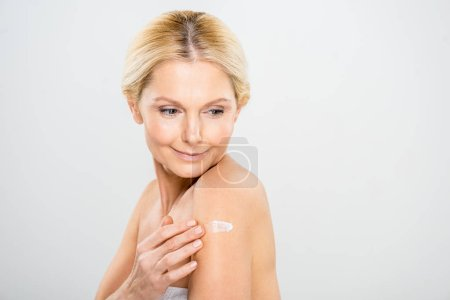 beautiful and mature woman looking down and applying cosmetic cream on shoulder