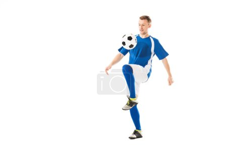 full length view of athletic young sportsman in soccer uniform training with ball isolated on white